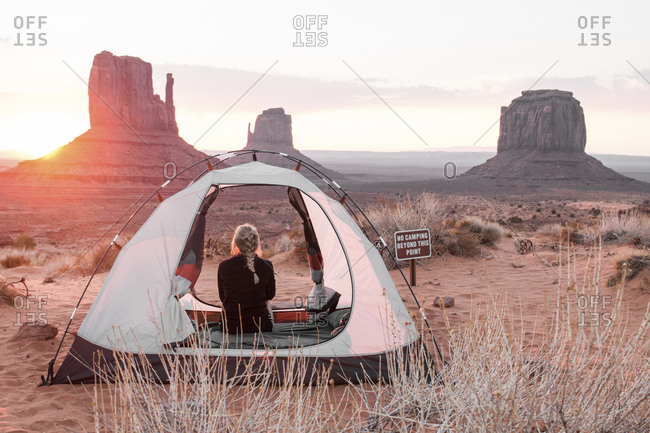 Rear view of woman sitting in tent against sky at Monument Valley Tribal Park during sunset