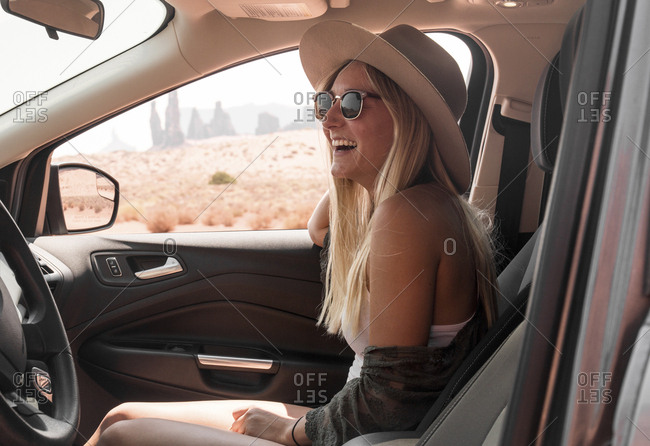 Side view of happy woman wearing hat and sunglasses while traveling in car at Monument Valley Tribal Park