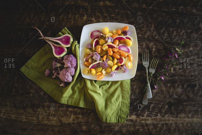 High angle view of salad served in plate with flowers and forks by napkin on wooden table