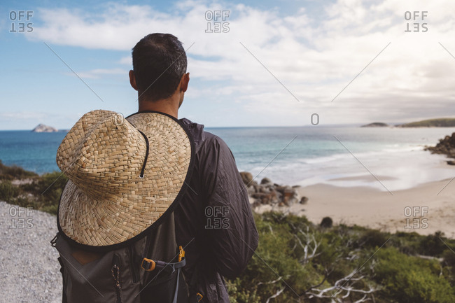 Rear view of hiker with straw hat and backpack looking at sea against sky in Wilsons Promontory National Park