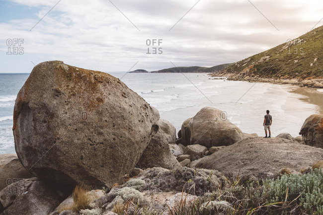 Rear view of hiker looking at sea while standing on rock in Wilsons Promontory National Park