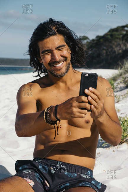 Happy shirtless man taking selfie with smart phone while sitting at Hyams Beach against sky during sunny day