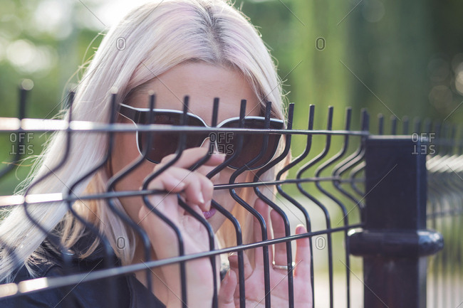 Close-up of blond hair woman wearing sunglasses by fence