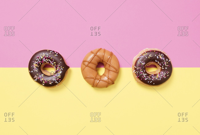 Overhead view of donuts arranged on colored background