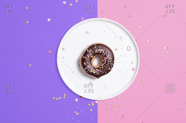 Overhead view of chocolate donut in plate with confetti on colored background