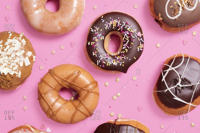 Overhead view of various donuts with confetti arranged on pink background