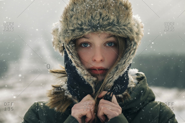 Close-up portrait of woman in warm clothing standing outdoors during snowfall