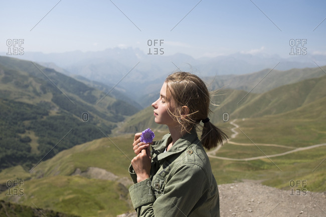 Side view of woman with eyes closed holding flower while standing on mountain against sky during sunny day