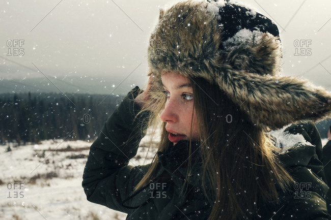 Close-up of woman in warm clothing looking away while standing on mountain against sky during snowfall