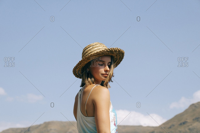 Side view of woman with eyes closed wearing hat while standing against blue sky during sunny day