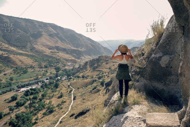 Rear view of woman looking at mountains while standing on rock against clear sky