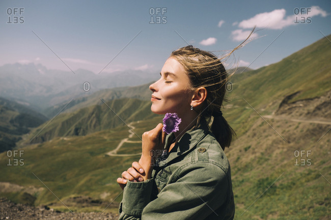Side view of smiling woman with eyes closed holding flower while standing on mountain against sky during sunny day