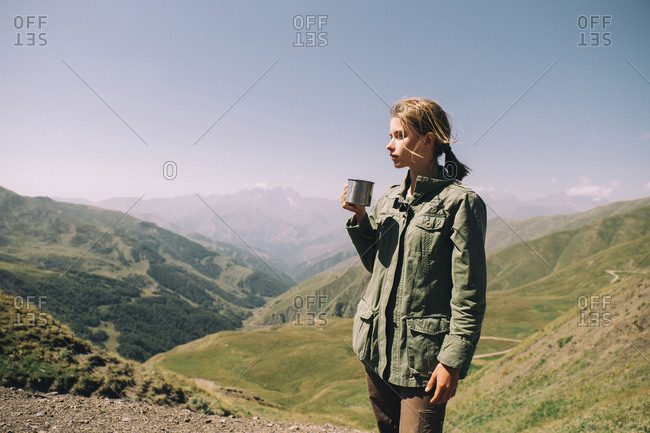 Woman having drink while standing on mountain against sky during sunny day