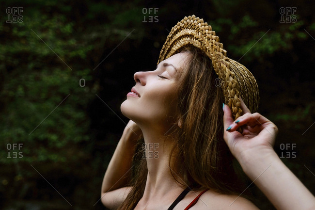 Close-up of smiling woman wearing hat while standing against trees in forest