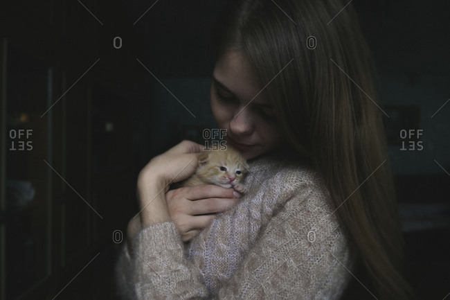 Close-up of woman holding cute kitten while standing in darkroom at home