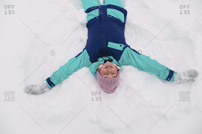 High angle view of woman with eyes closed making snow angel on field