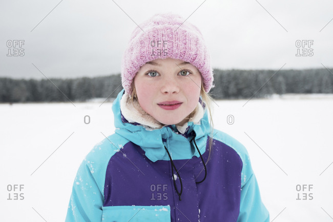 Portrait of woman standing on snow covered field against sky