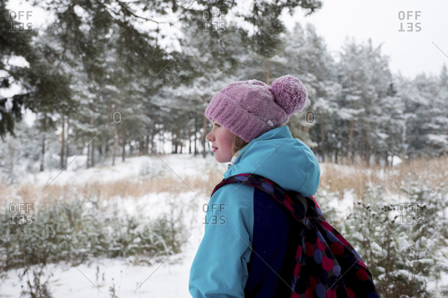 Side view of woman with backpack standing in snow covered forest