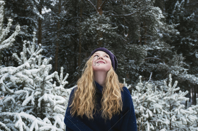 Happy woman with blond hair looking up while standing against trees in forest during winter