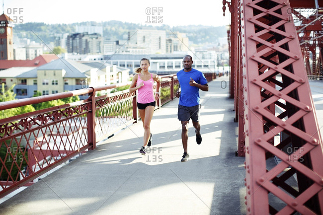 Confident athlete friends running on footbridge in city