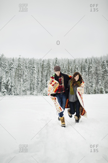 Happy couple with blanket running on snow covered field against sky in forest