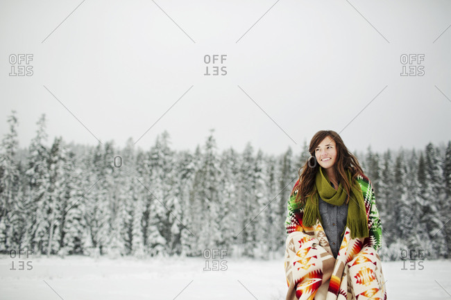 Low angle view of smiling woman looking away with blanket standing against sky in snow covered forest