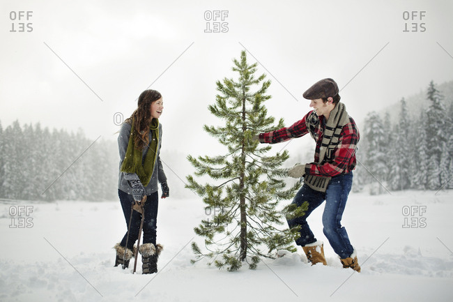 Happy couple standing by pine tree on snow covered field against sky in forest