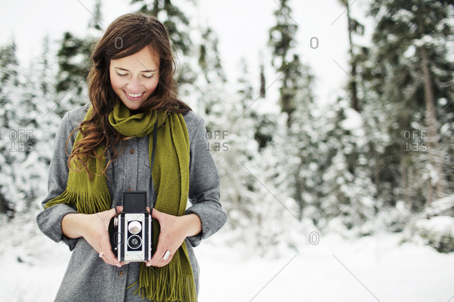 Smiling woman holding camera while standing against snow covered pine trees in forest