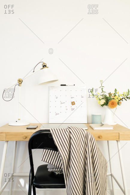Technologies with calendar and desk lamp by flower vase on table in office