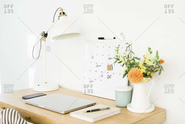 High angle view of technologies with calendar and desk lamp by flower vase on wooden table against wall in office