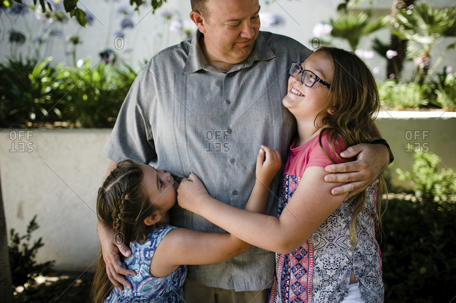 Happy daughters embracing father while standing at park
