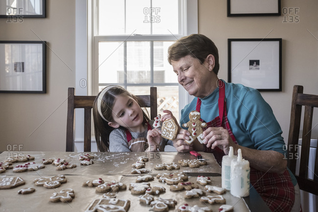Cute granddaughter showing gingerbread cookies to grandmother at home
