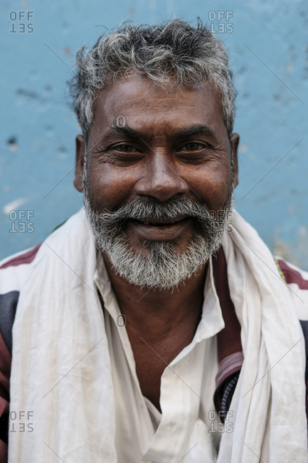 India, Himachal Pradesh, Parvati Valley - November 7, 2016: Portrait of smiling bearded mature man with white scarf against wall in town