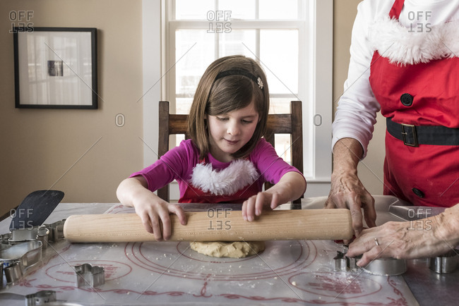 Granddaughter rolling cookie dough while sitting by grandmother at home
