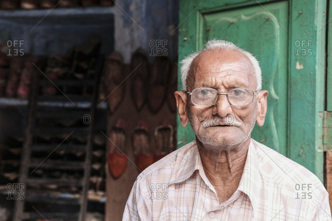 India, Rajasthan, Jodhpur - November 13, 2016: Portrait of senior shoemaker wearing eyeglasses against store