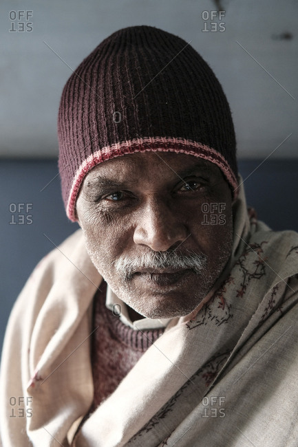 India, Rajasthan, Jaisalmer - November 18, 2016: Portrait of mature man wearing warm clothing in train