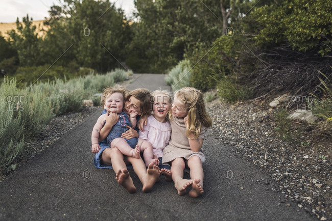 Happy cute sisters sitting on road in forest