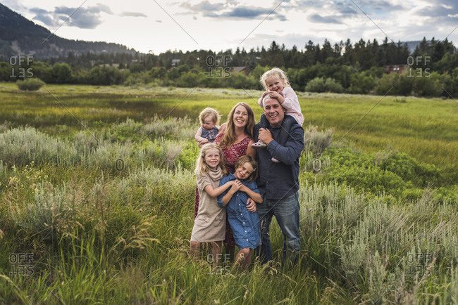 Portrait of happy parents with cute daughters standing on grassy field against sky in forest