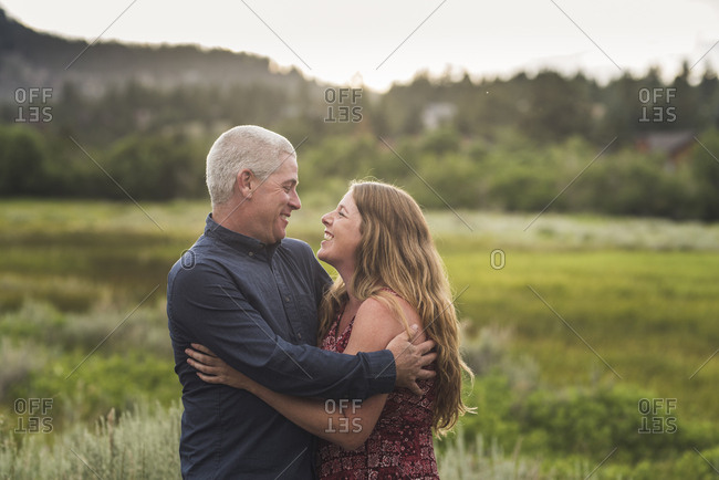 Happy couple with arms around looking at each other while standing on grassy field in forest