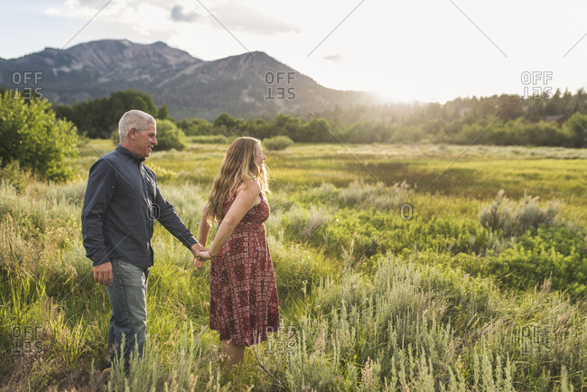 Couple holding hands while walking on grassy field against sky in forest