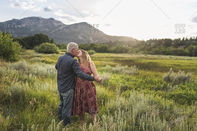 Romantic couple holding hands while kissing on grassy field against sky in forest
