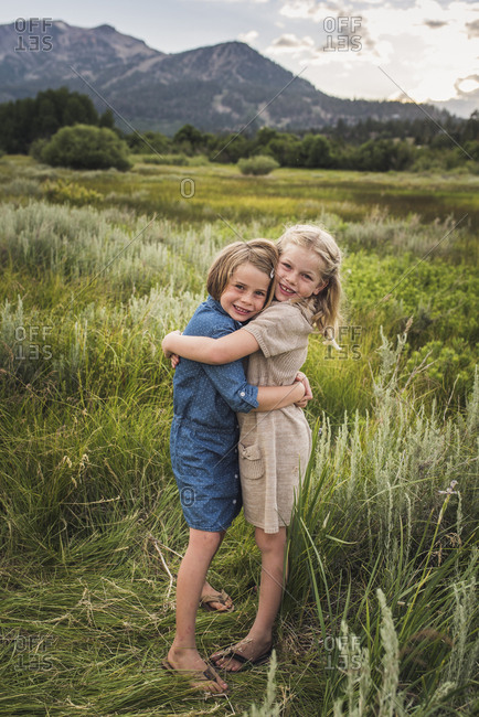 Portrait of happy sisters embracing while standing on grassy field in forest during sunset