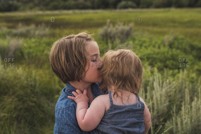 Side view of girl carrying sister while standing on grassy field in forest