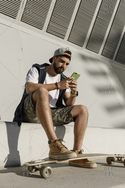 Low angle view of confident man using mobile phone while sitting with skateboard on retaining wall