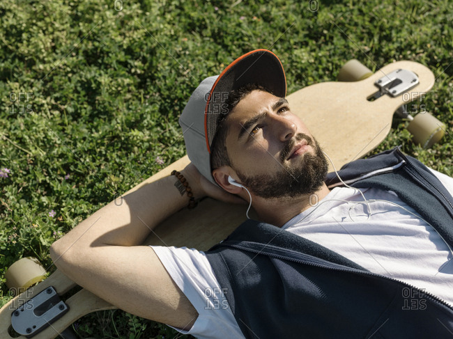 High angle view of thoughtful man with skateboard listening music while lying on grassy field at park during sunny day