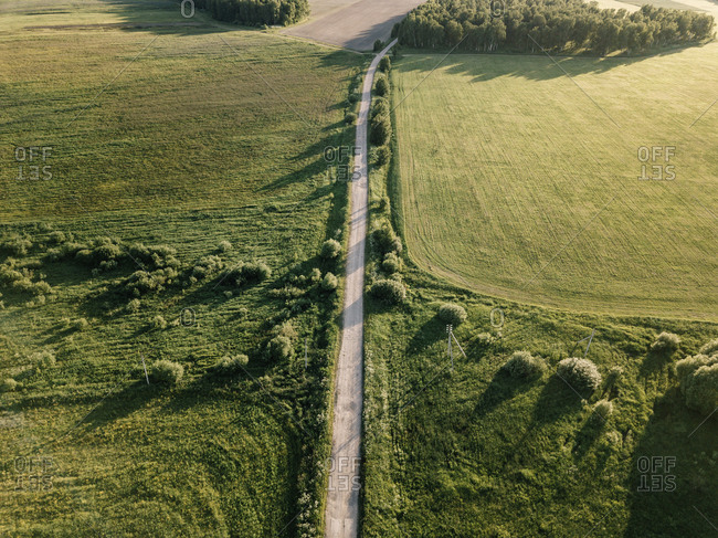 Aerial view of empty road amidst green landscape during sunny day