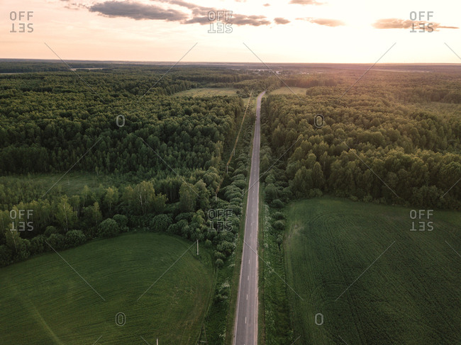 Aerial view of road amidst green landscape against sky in forest during sunset