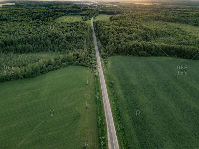 Aerial view of road amidst lush agricultural field during sunset