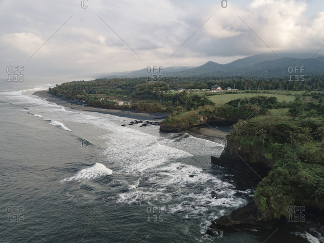 Scenic view of sea by landscape against cloudy sky at Bali