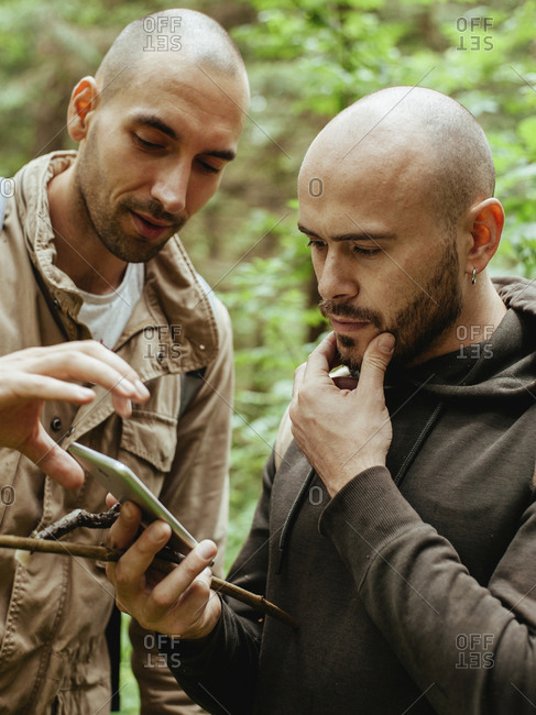 Friends using smart phone in forest